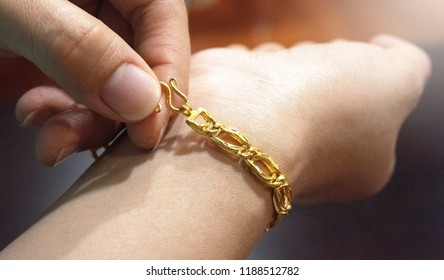 Woman wearing gold beautiful fashion bracelet close up picture with white ray light.