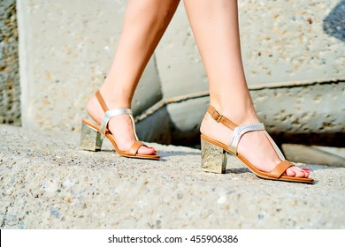 f59e8139cb3ef A woman wearing golden sandals is walking on concrete