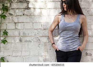 Woman wearing gray sleeveless t-shirt. White brick wall background.