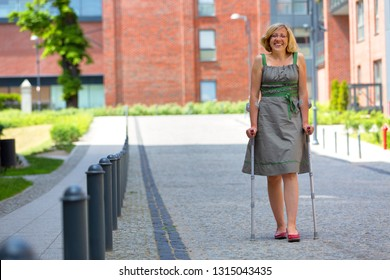 woman wearing green skirt practicing walking on crutches on the street and smiling