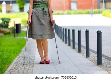 woman wearing green skirt practicing walking on crutches on the street