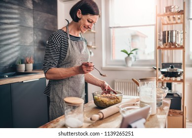 Woman wearing grey apron making apple pie on old wooden table