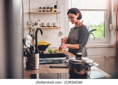 Woman wearing grey apron standing in the kitchen and cutting apples
