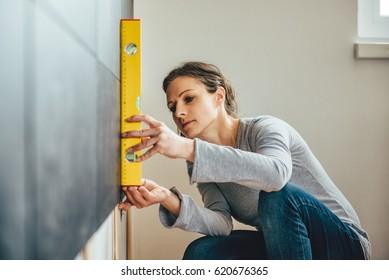 Woman wearing grey shirt using leveling tool at home