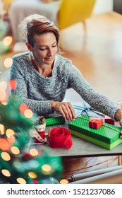 Woman wearing grey sweater sitting by the table in living room at home and wrapping Christmas presents