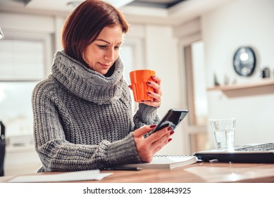 Woman wearing grey sweater using smart phone in the office and drinking coffee
