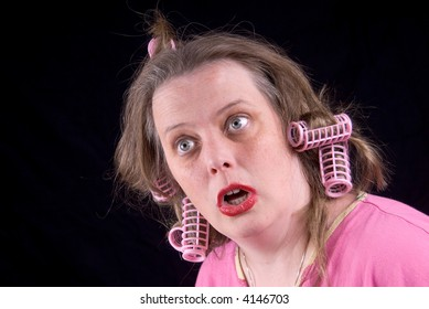 Woman wearing hair curlers and extreme makeup making a funny face isolated over black