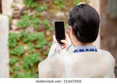 Woman wearing Hanbok, Korean traditional dress costume and taking photo with cell telephone or smartphone digital camera for Post Online on the Internet at walk and travel in Seoul city, South Korea