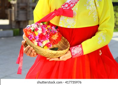 The woman wearing Hanbok, Korean traditional dress and holding a flower basket.