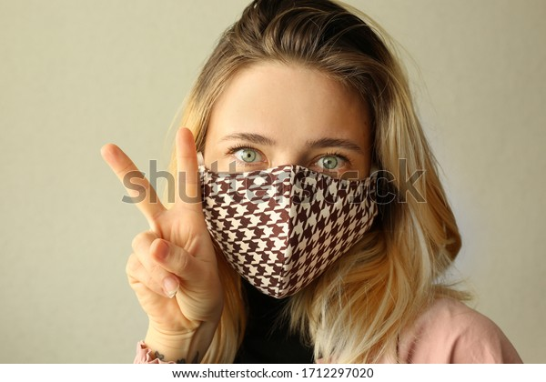 Woman wearing handmade cotton cloth face mask and making selfie at home. Corona virus concept. Quarantine concept. Reusable face mask.