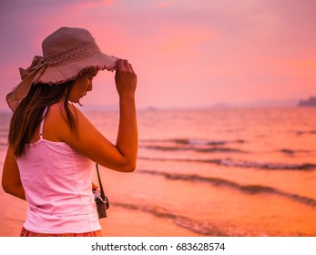 Woman wearing hat with beach dress under the sunset near by the sea, travel and holiday concept.