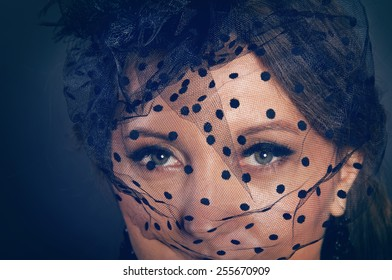 Woman wearing a hat with black veil with dots close up