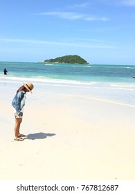 Woman wearing a hat, walking the beach, alone and lonely.