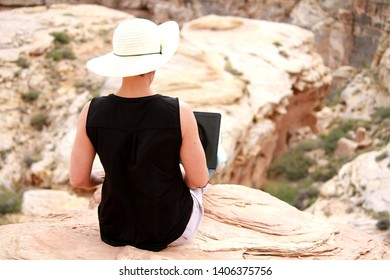A woman wearing a hat working remotely on her laptop computer on the edge of a cliff in Utah.