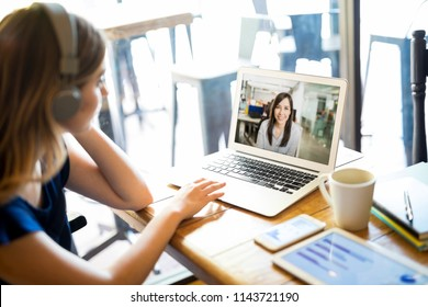 Woman wearing headphones and participating in a video conference call on a laptop while telecommuting from a cafe
