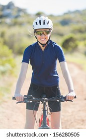 Woman wearing helmet on her bike looking at camera