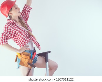 Woman wearing helmet and toolbelt. Girl working at flat remodeling. Building, repair and renovation.