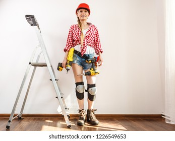 Woman wearing helmet, toolbelt standing on ladder using driil. Girl working at flat remodeling. Building, repair and renovation.