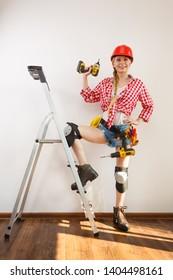 Woman wearing helmet, toolbelt standing on ladder using driil. Girl working at flat remodeling. Building, repair and renovation.