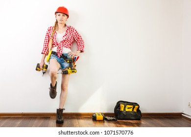 Woman wearing helmet using drill. Girl working at flat remodeling. Building, repair and renovation.