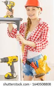 Mujer usando casco usando taladro. Niña trabajando en remodelación plana. Construcción, reparación y renovación.