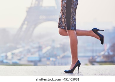 Woman wearing high heels shoes and walking near the Eiffel tower at early morning in Paris, closeup of legs