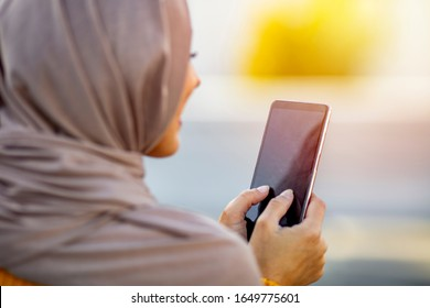 Woman wearing hijab browsing internet on mobile phone outdoors. Modern arabian girl using mobile phone on the street. Close up of beautiful woman wearing hijab smiling while texting on mobilephone