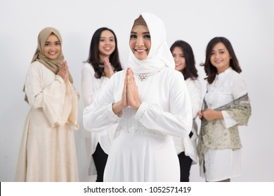 A woman wearing hijab standing and greeting in front of the camera. eid mubarak concept