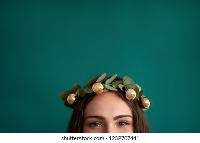 woman wearing holiday christmas flower crown with shiny baubles, creative DIY xmas