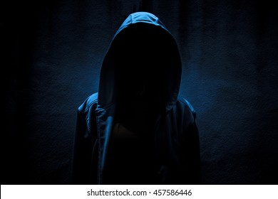 Woman wearing hoodie hiding in the dark,Scary background for book cover
