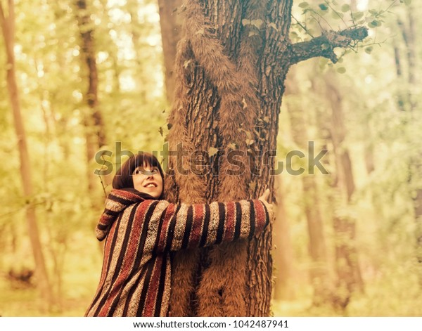Woman wearing hoodie hugging a tree in green forest