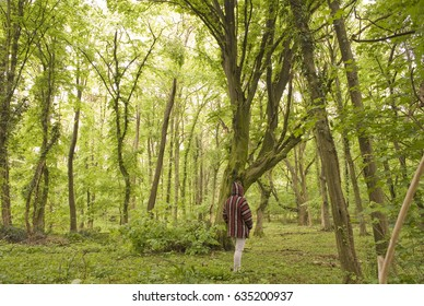 Woman wearing hoodie walking thru green forest