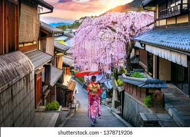 Mujer usando kimono tradicional japonés caminando en el distrito histórico de Higashiyama en primavera, Kioto en Japón.