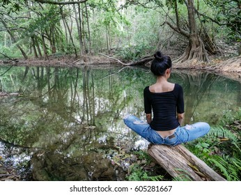 Woman wearing jean alone in beautiful nature, sadness and melancholy, trees reflection in water, meditation and loneliness.