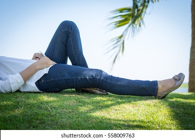 Woman wearing jeans Lying on the grass.