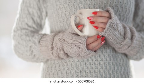 Woman wearing knitted sweater and gloves holding a cup of hot coffee, humorous home heating energy saving