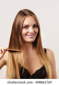 Woman wearing lace lingerie refreshing her hairstyle combing long hair with wooden comb. Health beauty and haircare concept
