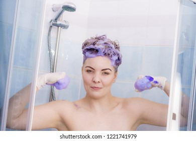 Woman wearing latex protective gloves while applying purple toner shampoo on her blonde hair. Haircare coloring at home concept.