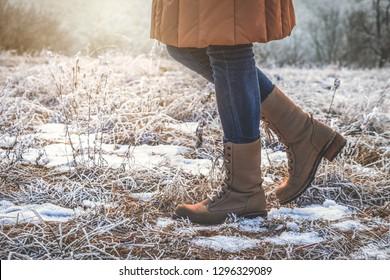Woman wearing leather hiking boots in winter frozen nature. Walking in snowy footpath