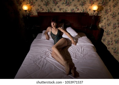 Woman wearing lingerie and lying in bed in a hotel room