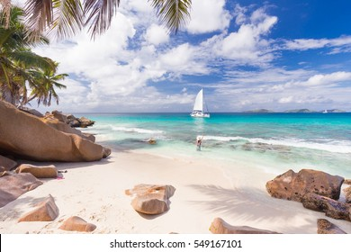 Woman wearing long floral summer dress and hat waving to people on the catamaran on Anse Patates beach, La Digue Island, Seychelles. Summer vacations on picture perfect tropical island concept.