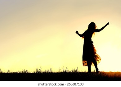 A woman wearing a long skirt, with long blonde hair, is dancing and praising God, while silhouetted against the evening sky