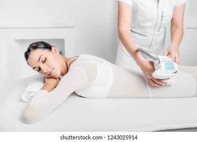 woman wearing lpg suite getting a lpg massage on her buttocks, selective focus