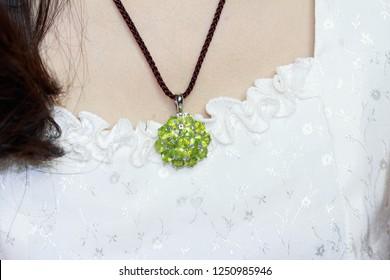 Woman wearing luxury silver jewelery necklace with green peridot gemstone