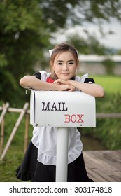 woman wearing maid costume with mail box