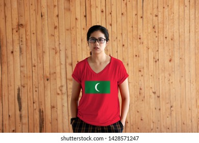 Woman wearing Maldives flag color shirt and standing with two hands in pant pockets on the wooden wall background, green with red border and white crescent on center.
