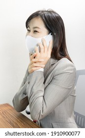 Woman wearing a mask calling for work with a smile