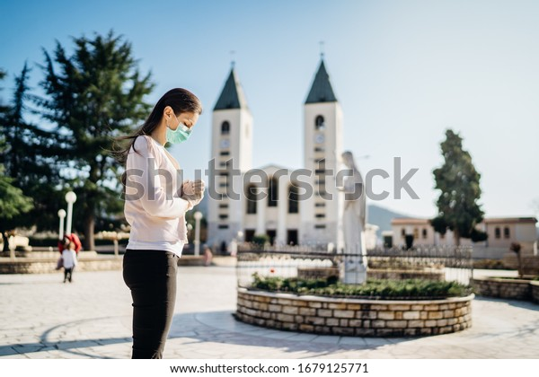 Woman wearing mask and gloves praying to God due to novel coronavirus covid-19 outbreak in Medjugorje.Woman in emotional stress and pain.Christianity.Strong religion,faith and hope concept