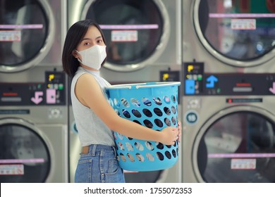 woman wearing a mask in quarantine for corona virus COVID-19 spreading outbreak. Doing laundry at laundromat shop during. New normal lifestyle social distancing for infection risk.