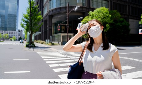 A woman wearing a mask wiping sweat from her face in the n the hot weather